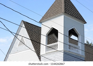Electrical lines cross the view of an old church and its bell tower.