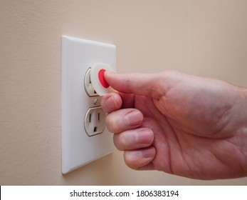 Electrical outlet with electricity safety cover to prevent child electrocution. Baby proofing household power sockets with plastic plug inserts.