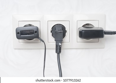 Electrical outlet with three black cords  close up