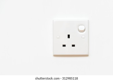 Electrical outlet in the UK, power socket on white wall with copy space