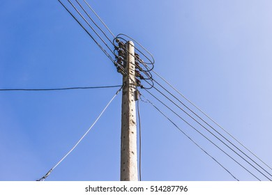 electrical post by the road against blue sky