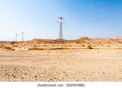 Electrical power lines on pylons in the landscape of the Middle East. Rocky hills of the Negev Desert in Israel.