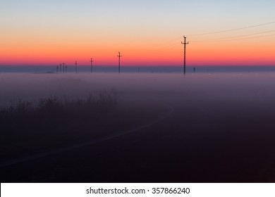 Electrical Power Lines and Pylons disappear over the horizon with Misty Sunrise, Sunset