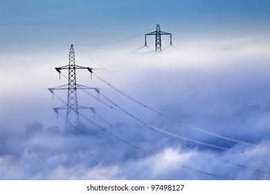 Electrical power lines and pylons emerging from the mist