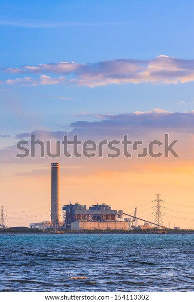 electrical power plant near the sea at sunset