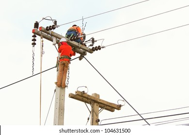 An electrical power utility worker in a bucket fixes the power line.