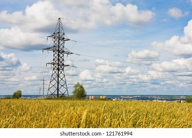 Electrical powerlines behind wheat field against a background of the sky in summer day