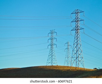 Electrical Powerlines on a Hill before a Blue Sky