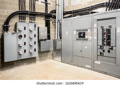 Electrical room of residential or commercial building. Multiple smart meters, main power breaker, meter stacks and cabinets. Perspective view