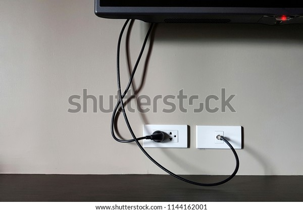 An electrical socket and TV outlet in the drywall in the room of in apartment,Electrical plug and TV signal outlets on white wall.