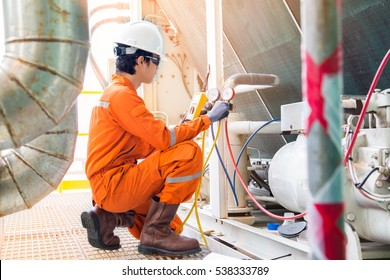 Electrical specialist checking Heating Ventilation and Air Conditioning system (HVAC) for preventive maintenance and while top up refrigerant to the cooling systems.