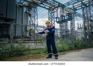 An electrical substation engineer inspects modern high-voltage equipment in a protective mask . Energy. Industry