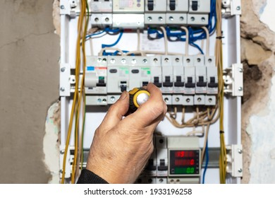 Electrical switchboard. A male electrician installs a multifunctional shield to control electricity into the wall of the house.