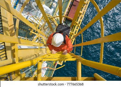 Electrical technician carrying tool bag and claim up to crane tower for troubleshooting electrical and instrument system of crane engine, offshore oil and gas industry.