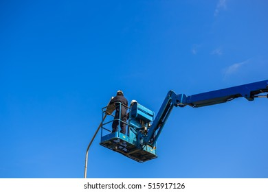 Electrical technician repairing street light by boom lift