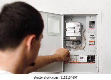 Electrical terminal box. man checking the electric control box. overload relay.