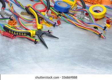 Electrical tools and component kit to use in electrical installations on grey metal background with place for text