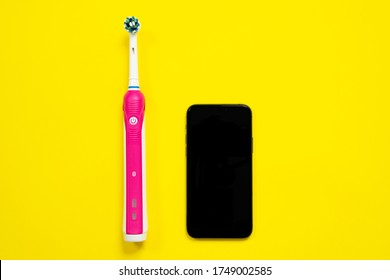 Electrical tooth brush of round shape and modern black mobile phone lying on bright yellow background. Possibility to manage the toothbrush with special smart app using phone. Studio, copy space.