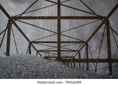 An electrical tower reflects in a puddle on the asphalt