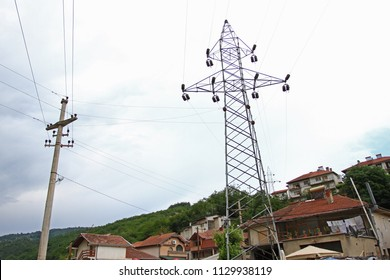 Electrical towers with wires for electricity in the center of the city. Electrical towers between houses. Metal poles of power lines. High-voltage direct current line. Power transmission towers.