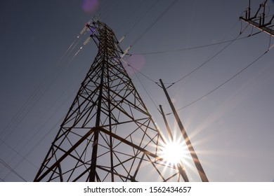 Electrical Transmission Line Tower with Sun Shining Through Glass Insulators