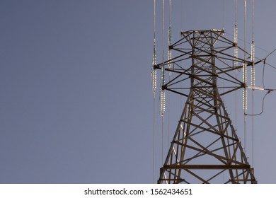 Electrical Transmission Line Towers with Sun Shining Through Glass Insulators