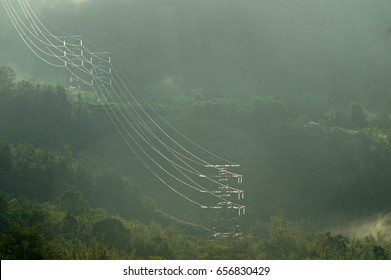 Electrical transmission tower cutting through hilly for forest of the interior area of Sabah during early foggy morning. Sabah grid supplies electric power to the interior of Sabah