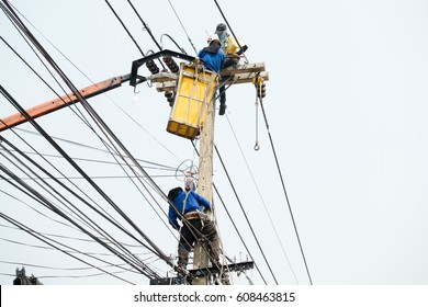 Electrical utility workers repairing problem with power line on the help of truck crane