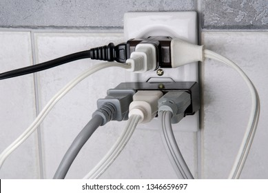 Electrical wall outlet overloaded with plugs