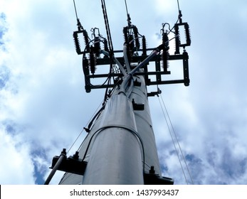 electrical wires on concrete pole end piece with cables vertically dropping under blue and white dynamic clear sky. overhead electrical cables and ceramic isolator cylinders. abstract view. technology
