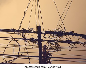 The electrical wires on the electrical poles in the city in the evening.