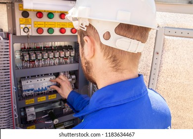 The electrician adjusts the electrical cabinet. engineer in helmet is testing electrical equipment. Maintenance of electric system. Worker diagnostic of automation panel