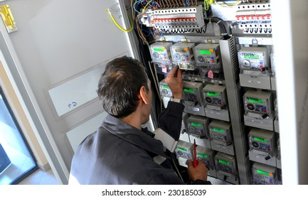 Electrician builder engineer inspecting electric counter equipment in distribution fuse box in building on Sofia, Bulgaria May 13, 2014