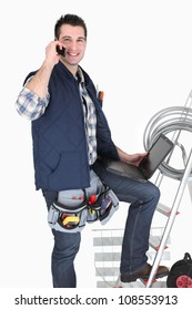 Electrician with a cellphone and laptop