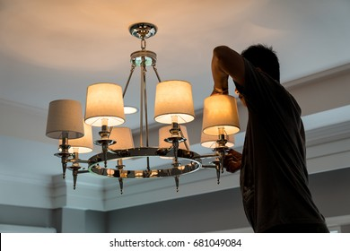 electrician change the light bulb of  chandelier on the ceiling