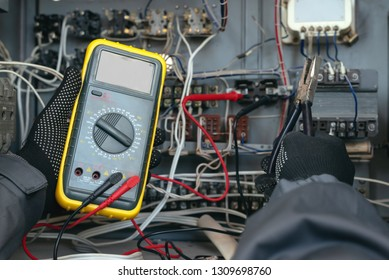 Electrician is checking the voltage in the electrical circuit of the installation with a multimeter. Electric works concept background.