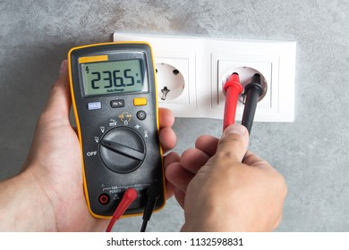 Electrician checking voltage in socket with tester. Professional multimeter in hand close-up.