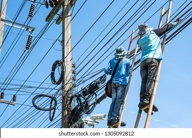 Electrician climbing the bamboo ladder to repair electric wires.
