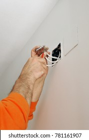 An electrician connecting the cables of the television antenna during the renovation of the house