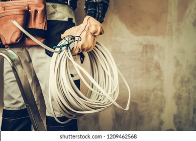 Electrician Contractor with Electric Cable Closeup Photo. Installing Whole New System.