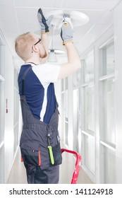 Electrician in Coverall Repairing Broken Light