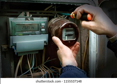 The electrician dismantles the old analog electricity meter. Near the installed digital counter.