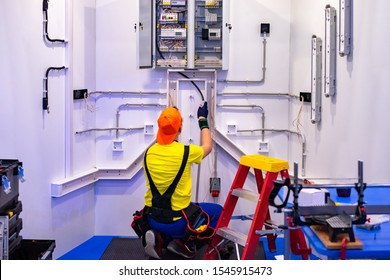 An electrician. Electricity installation in the house. A man is repairing electricity. Electrician at work. Worker repairs an electric cabinet. Electrical wiring repair. Electro shield.
