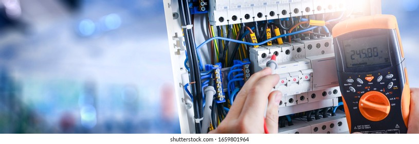 Electrician engineer installing and test electric connection wires of fuse switch box. Multimeter in hands of electricians detail. Wide banner or panorama photo.