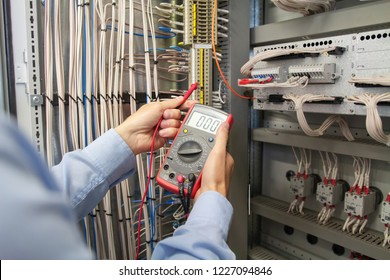 Electrician engineer with multimeter in electrical cabinet