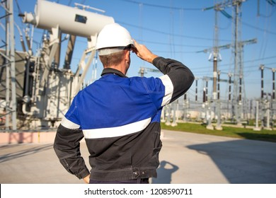 Electrician engineer on power electric station look at industrial equipment. Technician in helmet on electro substation. Examination high voltage devices