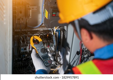 Electrician engineer tester measuring voltage and current of power electric line in electical cabinet control.Electrician use Digital Voltmeter Testing Voltage on automatic control box.Selective focus