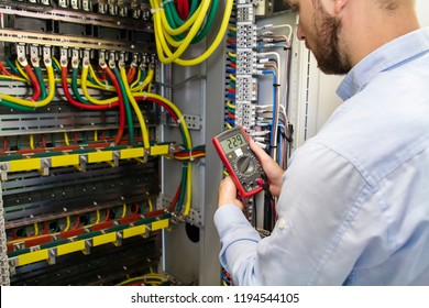 Electrician engineer testing cabling connection of high voltage power electric line in industrial distribution fuse board. Service man with multimeter. Tester in hands of electric worker