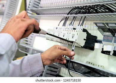 Electrician engineer wiring electrical installations and wires on relay protection system. Bay control unit. Medium voltage switchgear