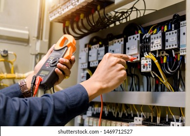 Electrician engineer work  tester measuring  voltage and current of power electric line in electical cabinet control. - Shutterstock ID 1469712527
